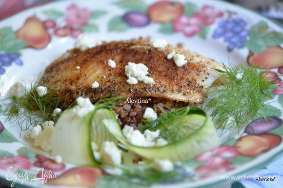 Огурец тонко полосками разрезаем пилером для овощей или ножом. Готовую тилапию выкладываем на гречку, сбрызгиваем лимонным соком, посыпаем сыром фета, рядом кладем огурец тонко порезанный и укроп. Приятного аппетита.
