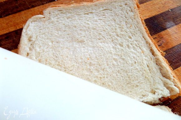Переворачиваем на доске сыром вниз и плотно раскатываем хлеб скалкой.