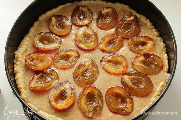 Наполнить корж кремом, разложить сверху половинки слив. Выпекать пирог около 30 минут при температуре 180 градусов.