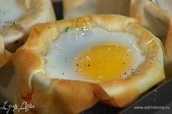Запекать яйца в разогретой духовке 10 минут, затем посолить и поперчить.