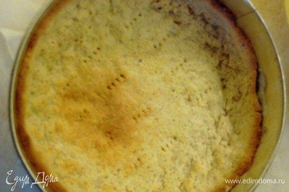 Разогреть духовку до 200 градусов Цельсия. Смазать сливочым маслом форму диаметром 26 см. (Можно взять и разъемную форму, но тогда лучше на дно положить пергамент для запекания.) Раскатать тесто в круг диаметром ~32 см. Выложить тесто в форму, сделав высокий бортик. В нескольких местах наколоть вилкой, чтобы лучше пропекалось, и поставить в духовку приблизительно на 20 минут (тесто должно стать немного золотистым).
