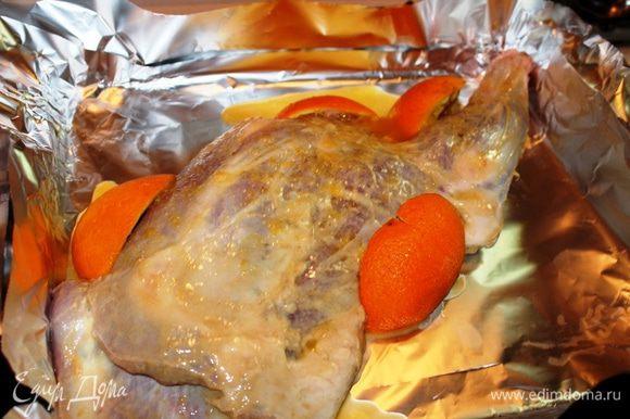 Духовой шкаф нагреть до 200 градусов. На противень застелить фольгу в два слоя, выложить на нее баранью ногу, залить соком апельсина (соком второй его половинки) и обложить апельсиновой кожурой