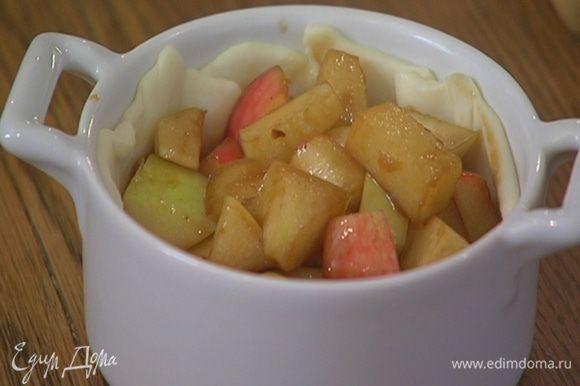 Меньшие кружки теста уложить в формы, сформировав бортики, выложить яблочную начинку, влить в каждую форму по 2 ст. ложки сливок.