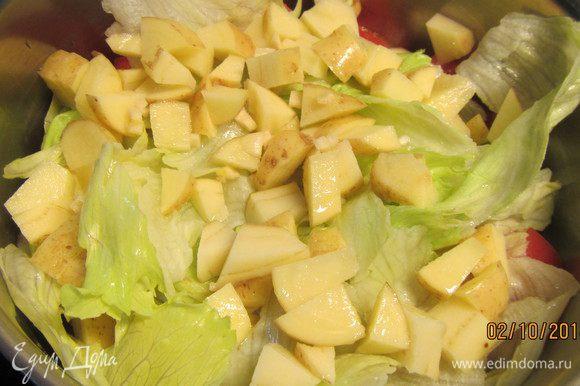 После этого добавляем измельченный чеснок, салат, огурец, помидоры и картофель. Все перемешиваем, солим, перчим по вкусу, добавляем лимонный сок. Накрываем крышкой и готовим на небольшом огне около 15 минут.