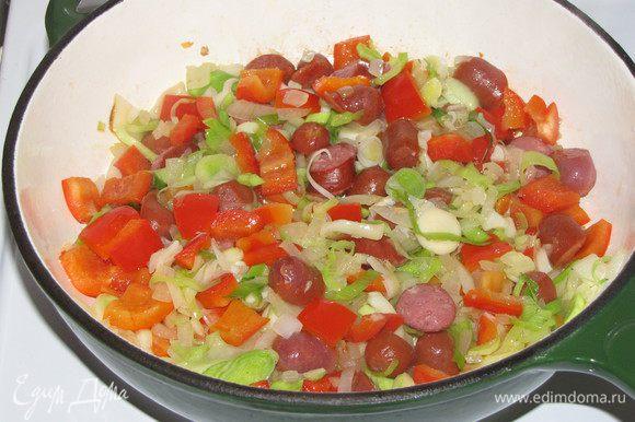 Добавить измельченный чеснок, лук порей, болгарский перец и колбаски. Перемешать и жарить 5 минут на небольшом огне.