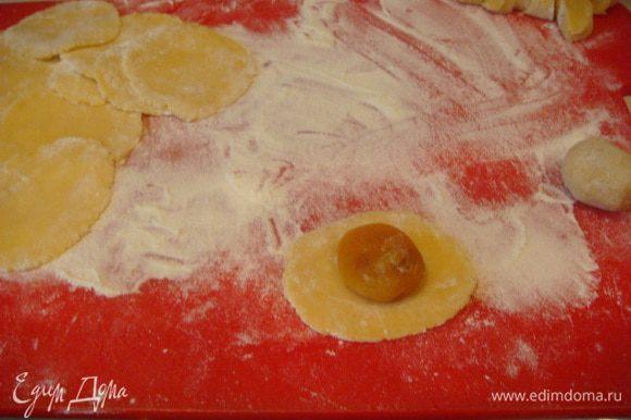 Тесто раскатать колбаской, нарезать на 44 части,раскатать и завернуть курагу,положить колобок в ладошку и слегка прижать,получаются ровные колобки.