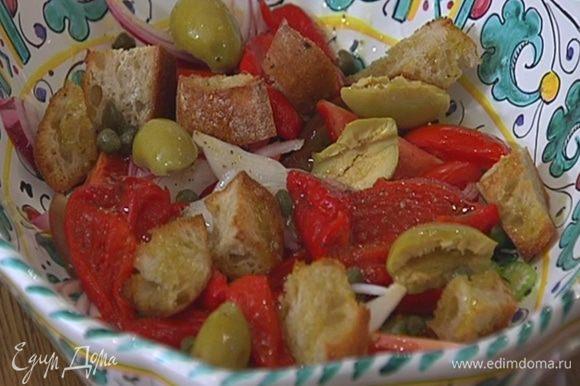 Сверху разложить сухарики из хлеба, оливки и каперсы, полить все оставшейся заправкой.