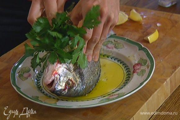 Дораду сбрызнуть оставшимся оливковым маслом, посолить и поперчить со всех сторон. В брюшко рыбы поместить петрушку, розмарин, тимьян и половину долек лимона.