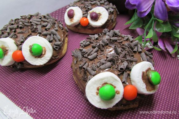 Смазать готовый «глаз» шоколадной пастой и приклеить его на булочку. Аналогично подготовить и второй глаз. Конфетку М&М другого цвета смазать шоколадной пастой и приклеить вместо носа.