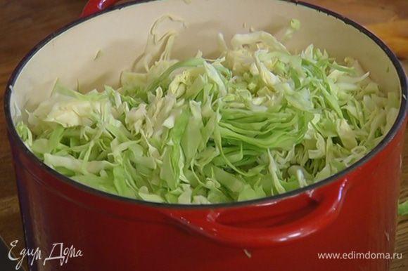 В кастрюлю к луку добавить квашеную и свежую капусту, перемешать и накрыть крышкой.