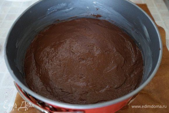 Дно разъемной формы выстелить пергаментом, смазать боковые стороны сливочным маслом. Выложить тесто, разровнять и поставить выпекаться в духовку на 20 минут. После выпечки, корж из формы не вынимать, оставить для остывания. Температуру в духовке понизить до 160 градусов.