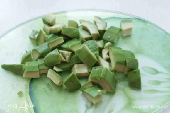 Из очищенного авокадо извлеките косточку, сбрызните мякоть соком лимона.