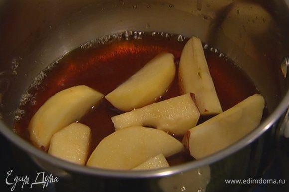 Оставшийся сахар всыпать в небольшую кастрюлю, влить 3 ст. ложки воды, добавить дольки яблок и закарамелизировать их.