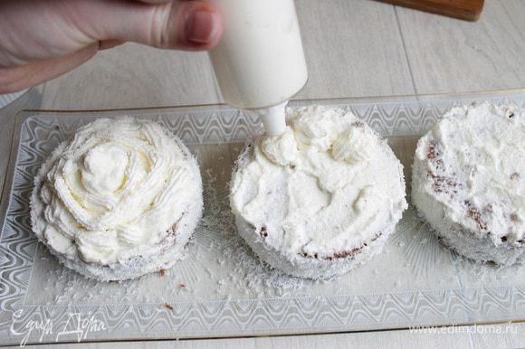 Затем сливки накладываем в кондитерский мешок и выдавливаем сверху пирожных. Украшаем еще любыми шоколадными фигурками и посыпаем слегка какао.