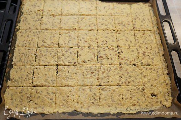 На противень постелить бумагу для выпечки (у меня тефлоновый лист), выложить тесто и аккуратно раскатать как можно тоньше – примерно 2 мм. Тесто очень липкое и можно раскатывать его между двумя листами для выпечки. Ножом нанесите бороздки для разделения кусочков, чтобы по ним потом разломать хлебцы. Посыпать крупной солью.