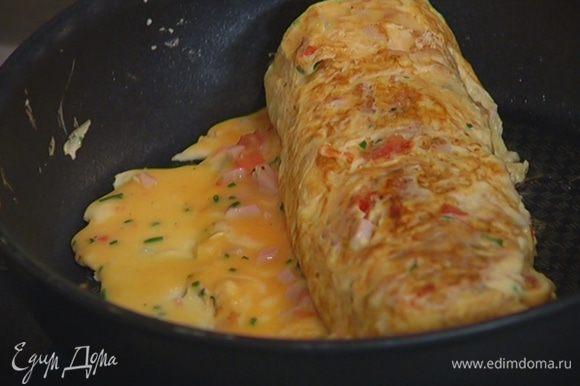Продолжая сворачивать омлет с одного края в рулет, порциями доливать оставшуюся яичную массу. При необходимости смазывать кисточкой сковороду оливковым маслом.