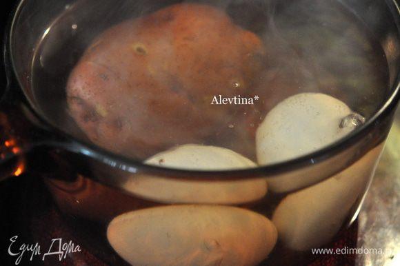 Отварить до готовности картофель и яйца. Очистить готовый картофель и порезать кубиками. Яйца очистить и порезать пополам.