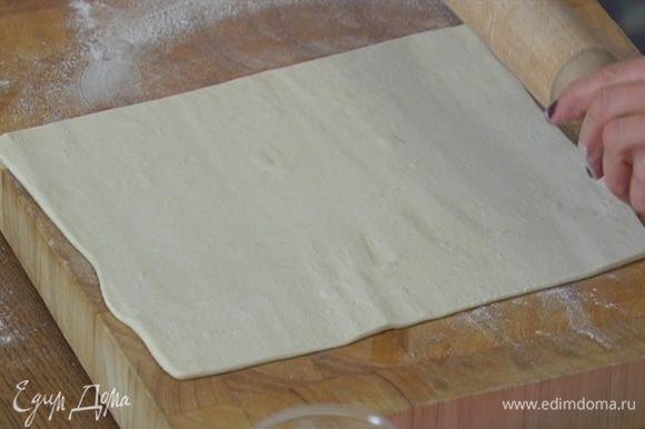 Рабочую поверхность присыпать мукой, немного раскатать тесто и вырезать круги диаметром чуть больше формочек.