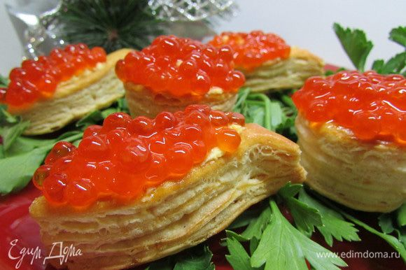Сверху украсить крем красной икрой. Выложить тарталетки на тарелку, украшенную зеленью петрушки или укропа. Приятного аппетита!