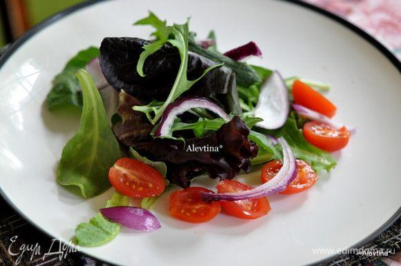 Разложим по тарелкам салатную смесь. Затем красный лук порезанный, помидоры шерри порезанные пополам.