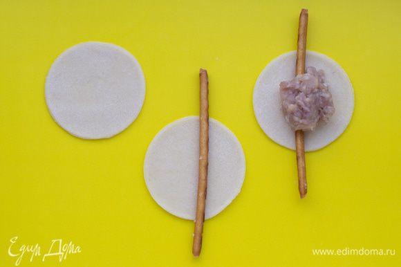 На каждый кружок из теста положить соленую соломку так, чтобы она на пару сантиметров выходила за края теста. В середину выложить фарш (примерно 1 ч.л. с верхом).