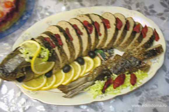 Остывшую рыбу нарезаем порционными кусочками, в глазницы вставляем маслины. Украшаем кусочками лимона, порезанными помидорами черри или по вашему усмотрению.