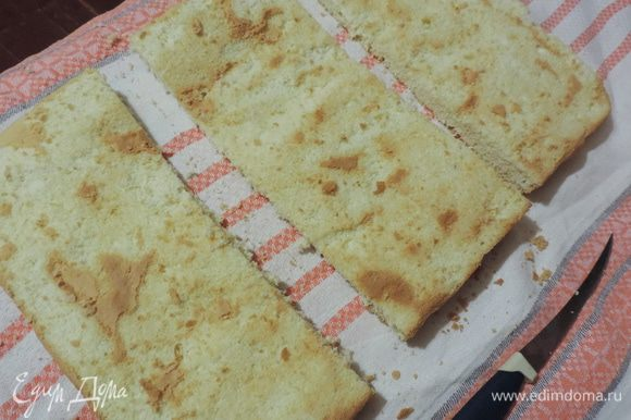 С остывшего бисквита аккуратно снимаем верхнюю запеченную корочку. Она нам пригодиться для посыпки. Подготовленный таким образом бисквит разрезаем поперек на три одинаковых пласта.