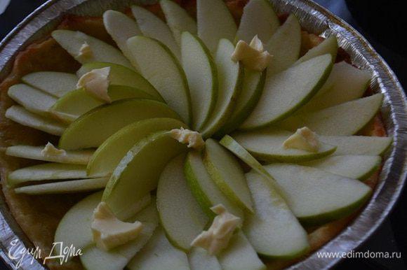 Достать пирог, удалить бумагу с бобовыми и уложить яблоки, сверху на яблоки кладем кусочки сливочного масла. Выпекать еще 20 минут. Растопить 100г сахара в кастрюле на небольшом огне, добавить яблочный сок и помешивая, варить до консистенции карамели. Достать пирог, полить его карамелью и снова поставить в духовку на 8 минут.