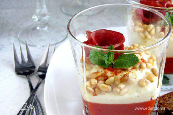 Перед подачей на стол в каждый стакан положить по ломтику сыровяленой ветчины и по паре листиков базилика (мяты). Посыпать тирамису поджаренными кедровыми орешками и приправить паприкой. Подавать охлажденным.