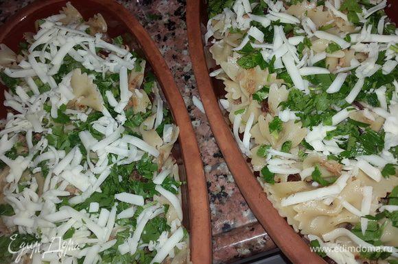 Пасту откинуть на дуршлаг и соединить с тунцом и томатами. Достать тарелки из духовки, выложить пасту, посыпать петрушкой и сыром и отправить в духовку на 3 минуты.