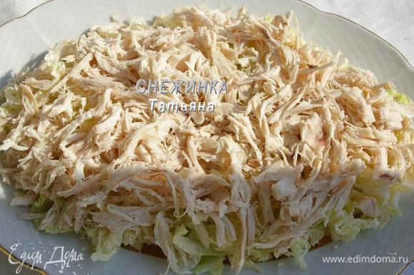 Капусту нарезаем тонко. Укладываем на общее блюдо первым слоем. Куриное филе разбираем на волокна. Кладём поверх капусты.