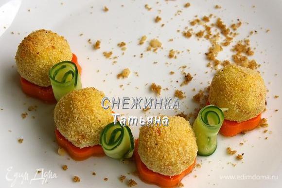 Блюдо для подачи посыпаем крошкой из хлеба и фундука. Выкладываем сливочно-морковную «подушку». На неё «колобки». Между «цветочками» ставим рулетики из огурца.