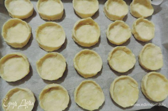 Тесто разделить на шарики размером с грецкий орех. Каждый шарик расплющить пальцами так, чтоб получить «тарелочку» с бортиками. Выложить печенье на противень, застеленный пергаментом.