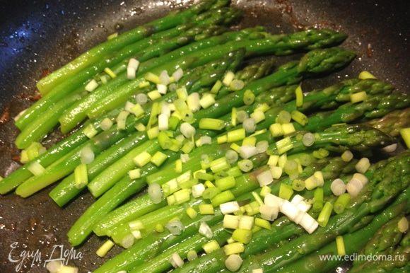 Выложить в сковороду спаржу с зелёным луком и слегка подрумянить.