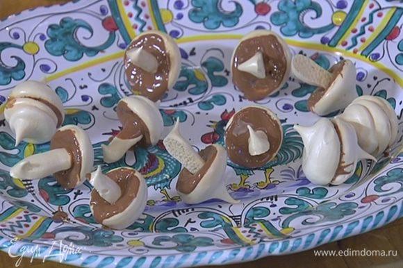 Плоскую часть круглых меренг смазать растопленным шоколадом и воткнуть ножки грибов — пока меренги теплые, это сделать легко!