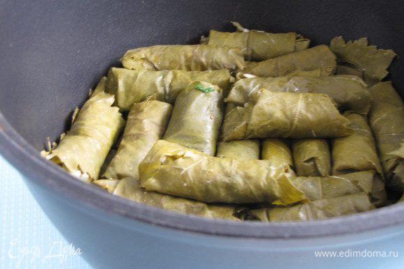 Дно сотейника выложите виноградными листьями, долму уложите плотно в сотейник в один или два ряда.