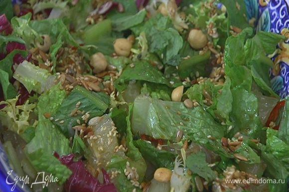 Посыпать салат обжаренным кунжутом, семечками и фундуком, украсить листьями мяты.