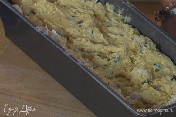 Продолговатую форму для выпечки смазать растительным маслом, выложить тесто и разровнять его.