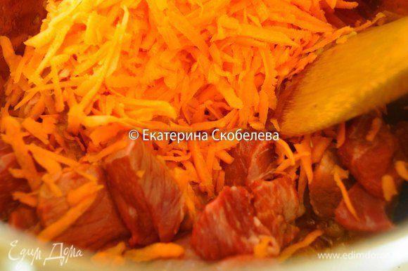 Тем временем помыть, очистить и натереть на крупной терке морковь. К луку выложить мясо, сельдерей, морковь и выдавленный через пресс чеснок. Постоянно помешивая, томить овощи и мясо 3-5 минут.