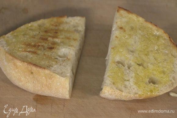 Хлеб сбрызнуть оставшимся оливковым маслом и обжаривать на сковороде, где жарилась котлета, до появления румяных полосок.