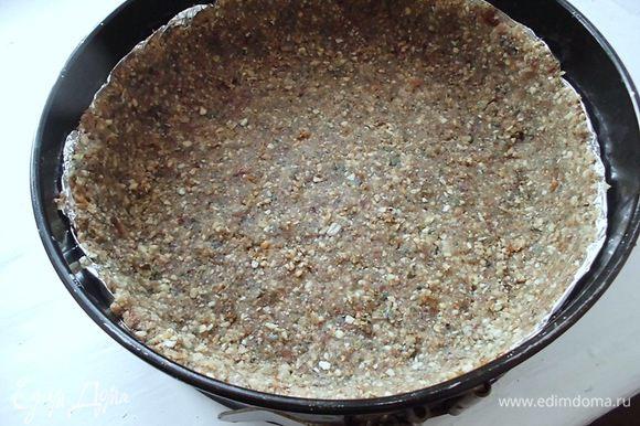 """Орехи и семечки измельчить с помощью мясорубки. Изюм также измельчить в мясорубке. Смешать с орехами и семечками, добавить кардамон, предварительно растертый. Добавить немного воды, чтобы масса схватилась. Форму (у меня разъемная, диаметром 20 см) застелить бумагой для выпечки или фольгой. Выложить основу, сделать небольшие бортики. У меня бортики оказались немного выше, чем я хотела. В следующий раз я бы сделала их пониже. И слой """"теста"""" тоже можно делать немного тоньше. Поэтому я все-таки посоветовала бы взять орехов поменьше, грамм 150, а, может, и 100! Готовую основу убрать ненадолго в холодильник."""