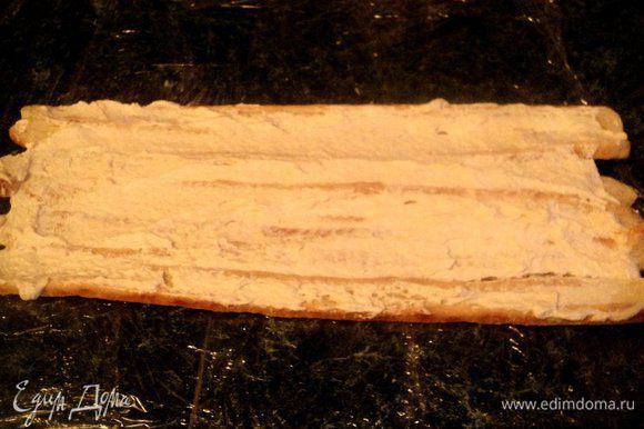 Сборка рулета: на столе застелить несколько слоев пищевой планки, выложить плотно несколько полосок слоеного тест, смазать сверху кремом.