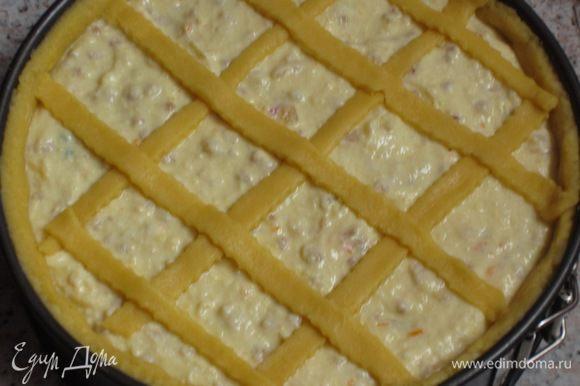 Оставшееся тесто раскатать, нарезать полоски шириной 1,5 см и выложить в виде решётки на пирог.