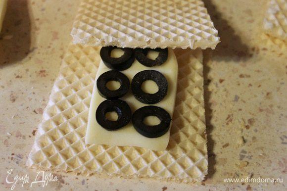 Теперь берем один вафельный квадрат, кладем на него ломтик сыра, 6 кружочков маслин, накрываем вторым вафельным квадратом. Обмакиваем с двух сторон в кляре и обжариваем на среднем огне с двух сторон до золотистой корочки.