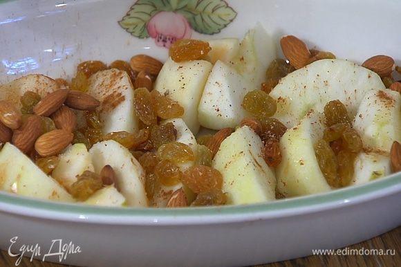 Яблочные дольки выложить в жаропрочную керамическую форму, сбрызнуть лимонным соком, посыпать изюмом, корицей и мускатным орехом.