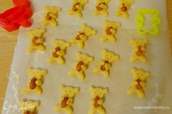 Раскатать тесто до толщины 5 мм, охладить и вырезать мишек. Вложить им в лапки миндаль. Иголочкой наметить глазки и носики.