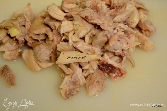 Затем куриные кусочки достанем шумовкой. Снимем кожицу, она нам не нужна, уберем кость и мясо порежем кусочками. У меня количество всех ингредиентов чуть меньше, чем по рецепту.