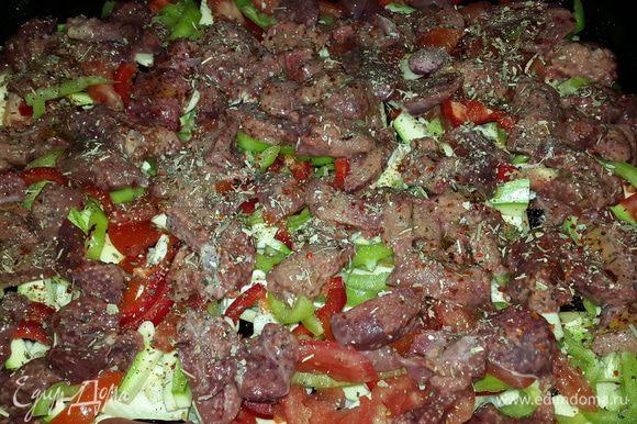 Печень промываем под проточной водой, убираем жир и ненужные жилки и режем небольшими кусочками. Выкладываем печень на овощи, солим, перчим двумя перцами, посыпаем сушеным базиликом, сбрызгиваем оливковым маслом, отправляем в духовку на нижний уровень и включаем её на 200 С.