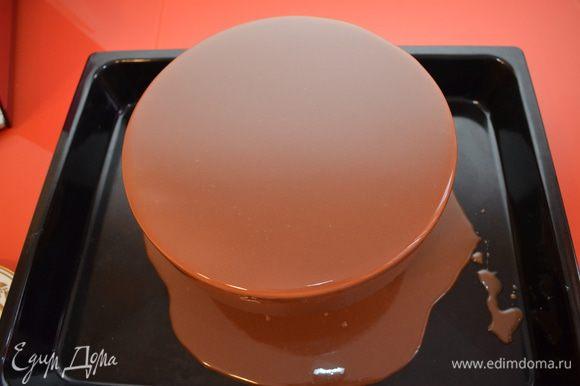Готовим глазурь: желатин замачиваем в холодной воде, шоколад растапливаем. Глюкозу и воду нагреваем до объединения, добавляем сахар и нагреваем до 103С, снимаем с огня. Добавляем желатин и сгущенку, перемешиваем и вливаем в эту массу растопленный шоколад. Дальше очень важный момент — пробиваем глазурь блендером. Это нужно делать в глубокой чаше. Блендер опускаем в глазурь, чашу немного наклоняем набок, включаем блендер и просто держим его, не поворачивая, не поднимая-опуская. Блендер сам пропустит глазурь через лезвия и вы получите гладкую массу без пузырьков, сито вам также не понадобится. Рабочая температура глазури 35-40С. Замерзший торт покрываем глазурью, установив его на решетку. Работать с глазурью надо быстро и чётко. Начинаем покрывать от центра и круговыми движениями переходим к бокам. Излишки глазури снимаем одним движением спатулы от себя. Чем быстрее вы будете работать, тем ровнее ляжет глазурь!