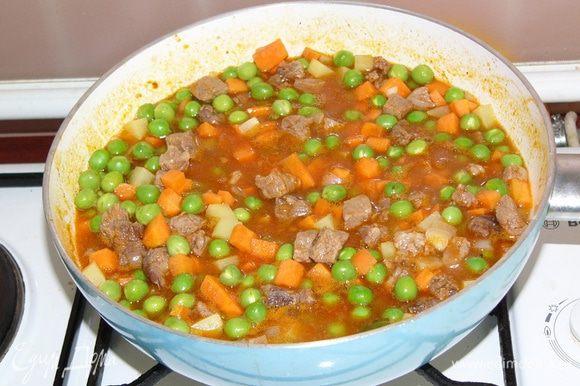 Как только мясо стало мягким, добавляем нарезанные овощи и горошек, при необходимости подливаем горячей воды. Тушим еще 15 минут. Солим.
